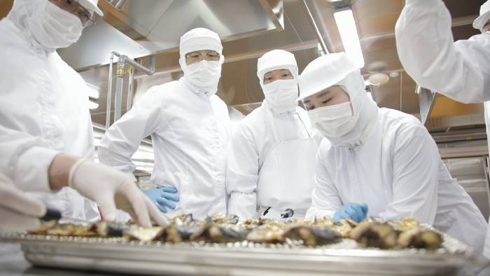 Employees at the Jungbu branch of CJ Freshway's Central Kitchen, located in Icheon, Gyeonggi-do, examine grilled fish cooked for demonstration purposes